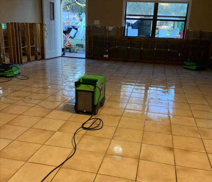 Wet floor, flood cuts, and green equipment on floor.