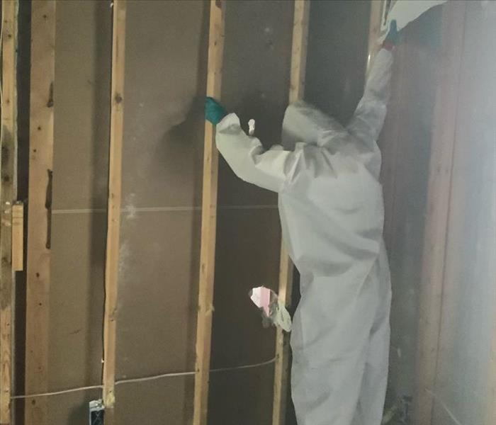 man in hazmat suit rips wall down during restoration