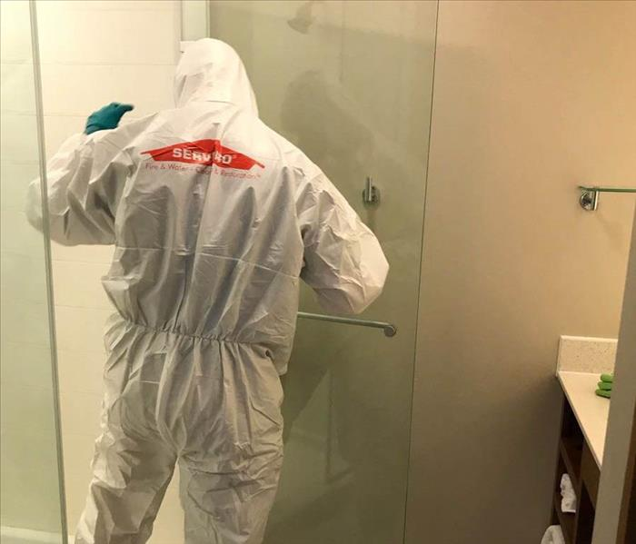 man in hazmat suit disinfects shower
