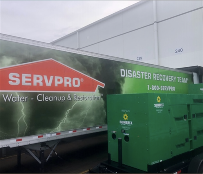 A Disaster Recovery Team trailer parked outside a commercial building with large loss equipment beside it.