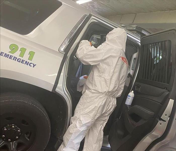 hazmat suit wearing man disinfecting 911 emergency vehicle