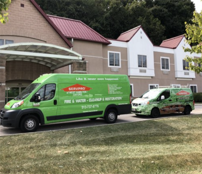 SERVPRO vehicles parked outside structure.